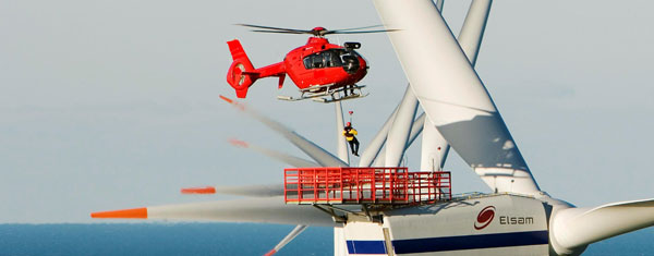 Helicopter lowering man onto wind turbine platform